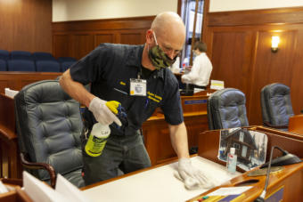 Nathan Paris cleans the desks on the floor of state House after legislators held a session on Monday, May 18, 2020, in Juneau, Alaska. (Photo by Rashah McChesney/KTOO)