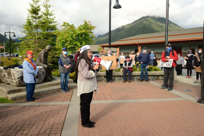 Alaska Native Sisterhood Grand President Paulette Moreno speaks to a crowd gathered around the Alexander Baranov statue in front of Sitka's Harrigan Centennial Hall on Tuesday. Protesters are asking the city to relocate and replace the monument. (Berett Wilber/KCAW)