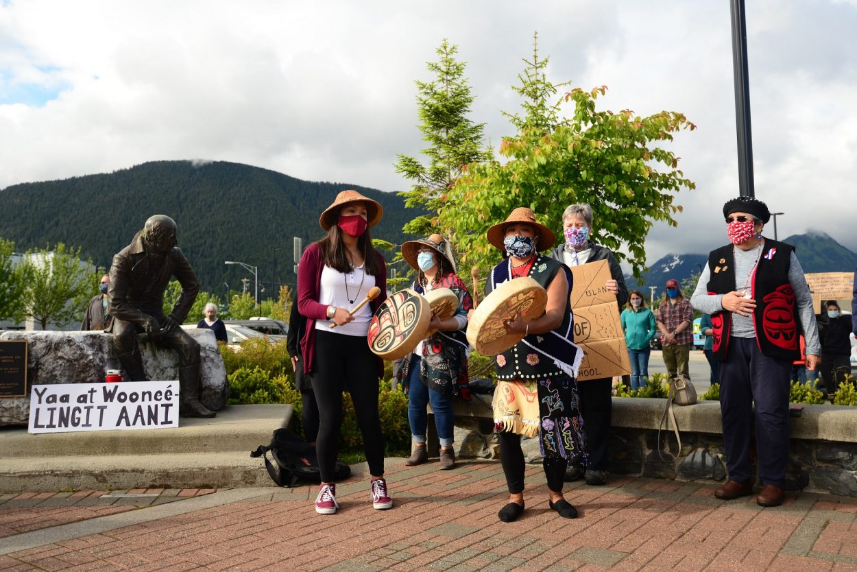 "Dionne Brady-Howard, whose Tlingit name is Yeidikoo'aa, drums and leads a song after speaking to the crowd about why she wants the city to relocate the statue of Alexander Baranov: ""No, it is not about political correctness. It is about accuracy. The teaching of accurate history is the only thing that keeps us from repeating those mistakes."" (Berett Wilber/KCAW)"