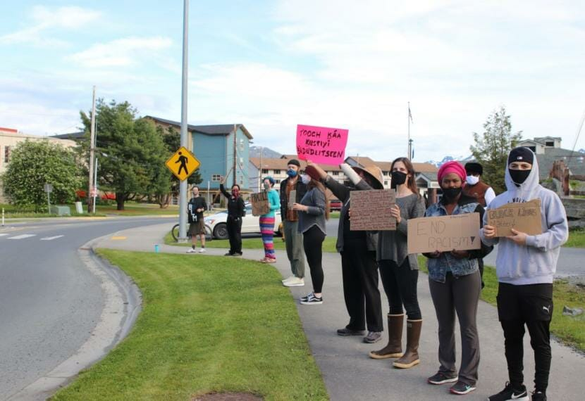 """Demonstrators stand in Sitka's main roundabout in solidarity with the Black Lives Matter movement earlier this month. """"It's important that this isn't seen as a trend, and it isn't seen as a one time thing,"""" demonstrator Devan Parsly said. """"So, we intend on doing it for as long as we need to."""" (Erin McKinstry/KCAW)"""