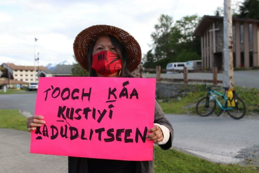 """Louise Kh'asheechtlaa Brady holds up a sign written in Tlingit at a local Black Lives Matter protest in Sitka. She's in agreement with the calls to """"defund"""" the police and wants to see more funding for social services, mental health care and drug and alcohol treatment instead. (Erin McKinstry/KCAW)"""