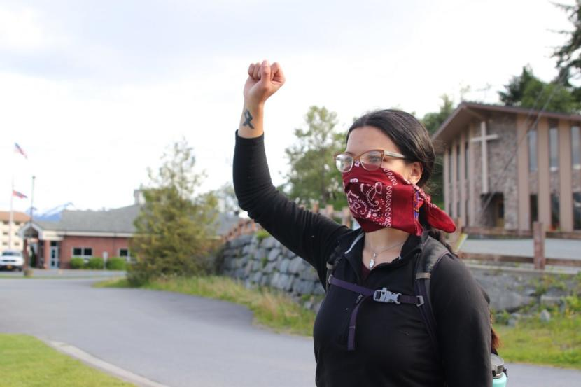 A demonstrator holds up her fist in solidarity with the Black Lives Matter movement at Sitka's main roundabout. (Erin McKinstry/KCAW)