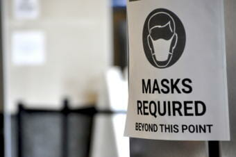 A sign at the Ted Stevens Anchorage International Airport near where people can get tested for COVID-19 (Liz Ruskin/Alaska Public Media)
