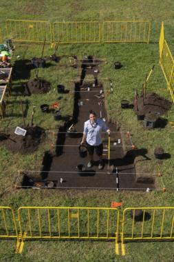 Tlingit and Unangax̂ visual artist Yéil Ya-Tseen Nicholas Galanin stands inside his artwork, an outline of a grave dug for a statue