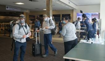 Screeners working for Capital City Fire/Rescue check paperwork and go through out-of-state travelers' options and obligations to fulfill COVID-19 health mandates at Juneau International Airport on June 26, 2020.