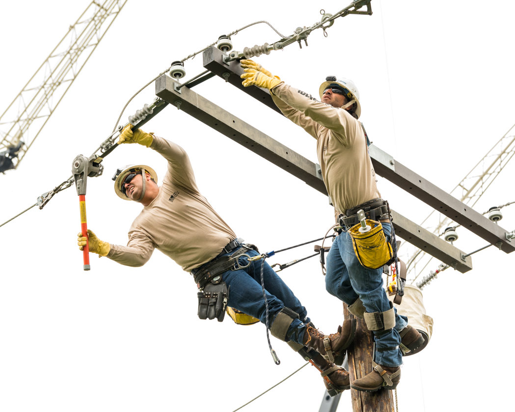 Two lineworkers atop a power pole, making repairs.