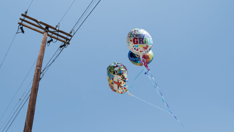 Two Mylar balloons in the sky flying near power lines.
