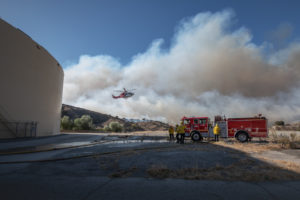 Image of a fire truck, firefighters and a helicopter in the air