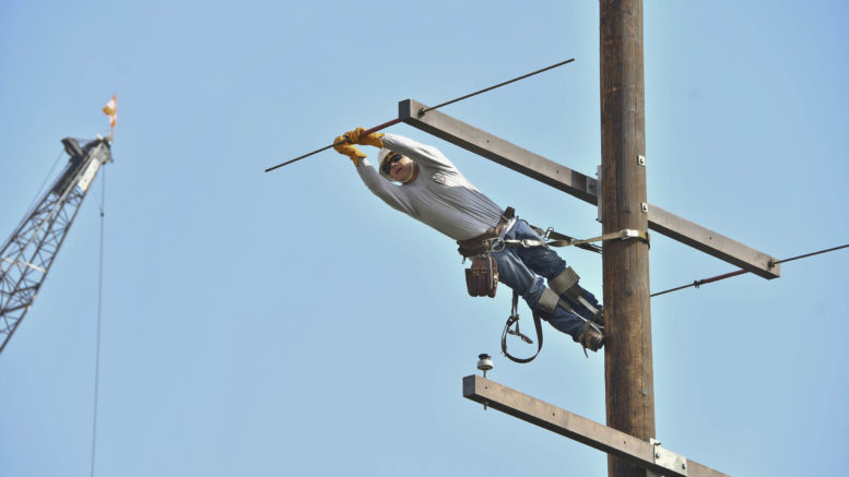 A lineworker in jeans, white shirt and a hardhat leans sideways off of a power pole to make repairs.