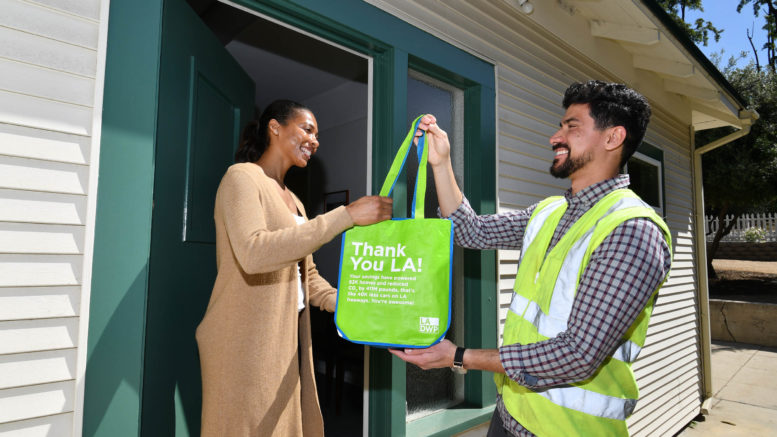 Image of a gentleman in flourescent work vest handing a bag of energy-efficient LED lightbulbs to a customer