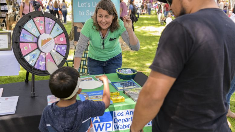 LADWP volunteer worker speaking with a young boy and his father at a booth