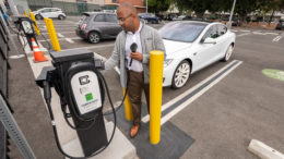Man in gray sweater holding electric vehicle charger. White EV in the background.