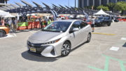 A silver electric vehicle in a parking lot during a test drive event.