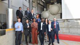 """Eleven people in suits standing on and near a an outdoor staircase, holding a """"thumbs up."""""""