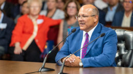 GM Marin Adams, in blue suit, in glasses, sitting, speaks into a microphone at a meeting.