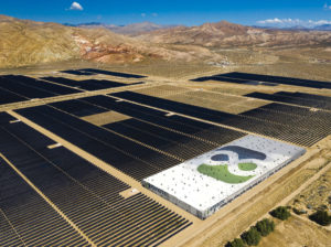 Image of rendering of large solar farm and battery storage units with mountain range in background.