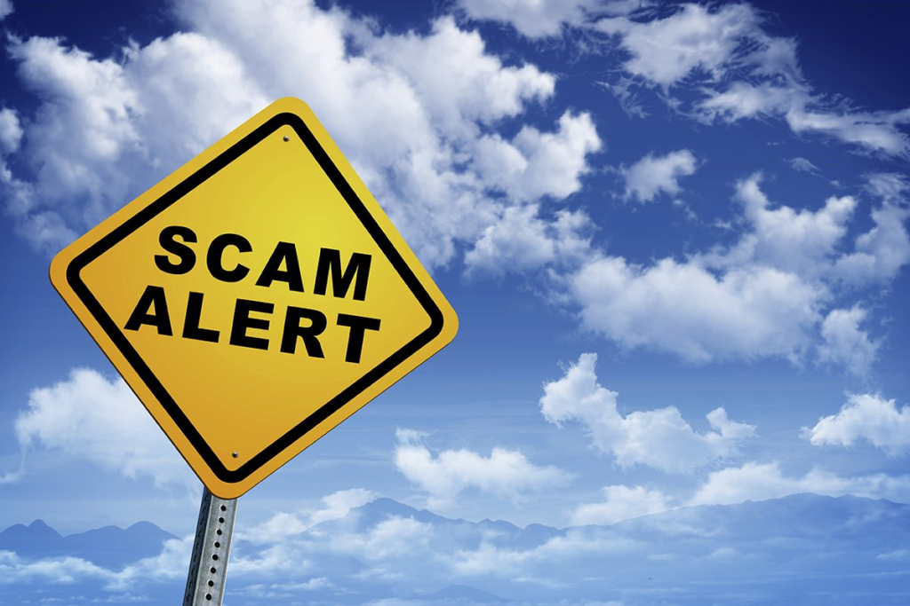 Image of a yellow sign that reads scam alert