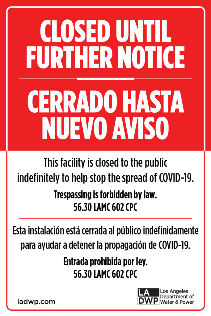 Red and white sign in English and Spanish reading reading Closed Until Further Notice