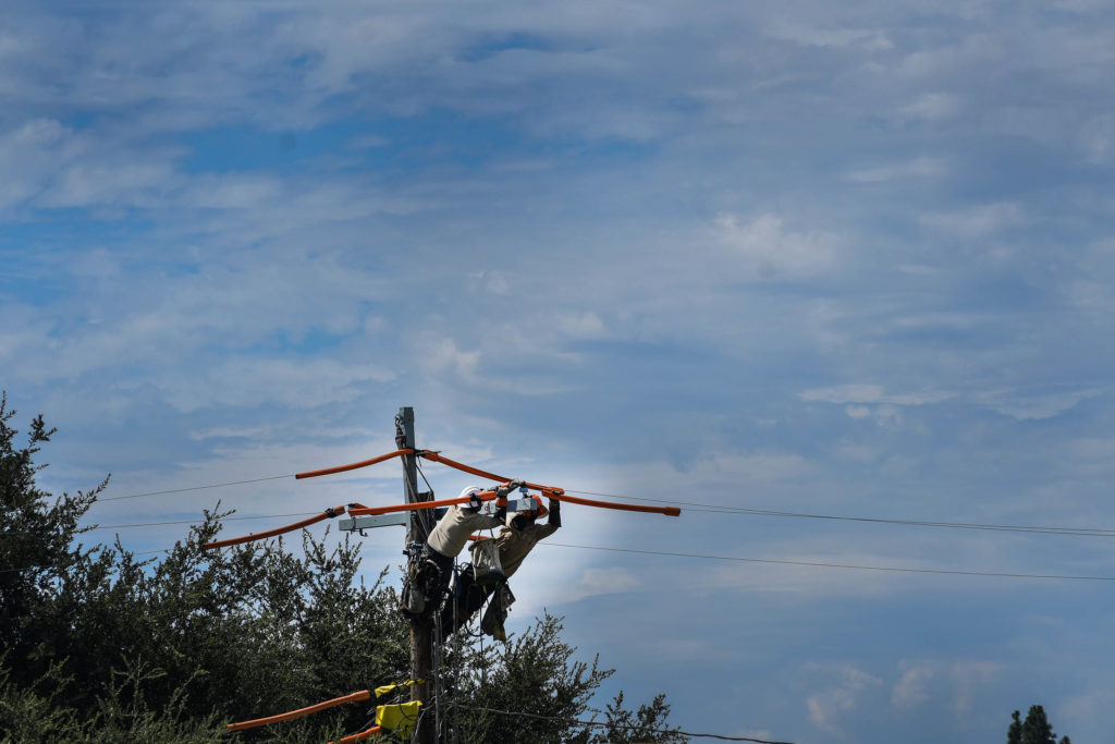 Image of two lineworkers repairing a power pole.