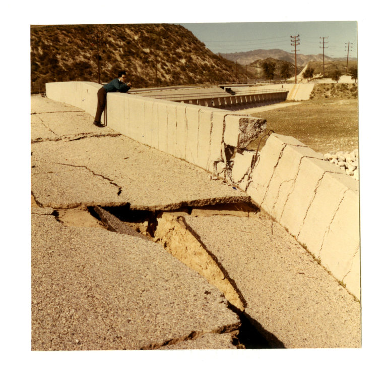 Image of a man looking over the edge of a damaged water dam