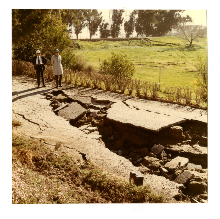Image of two men wearing hard hats looking at a sunken road due to an earthquake