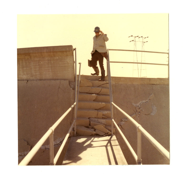 Image of a man wearing a hard hat going down damaged stairs