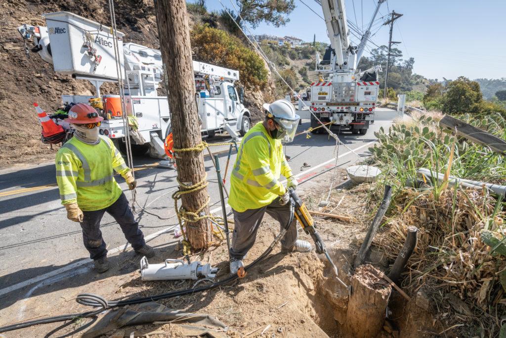 Crews making repairs to stump on hillside.
