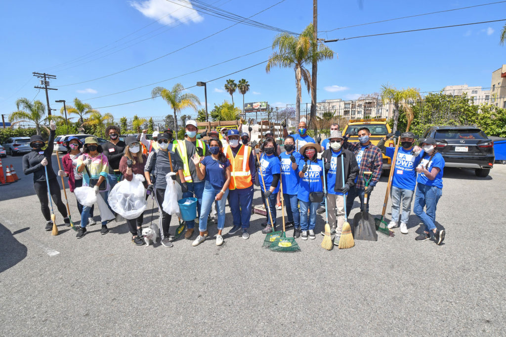 Image of a group of people with trash bags and brooms