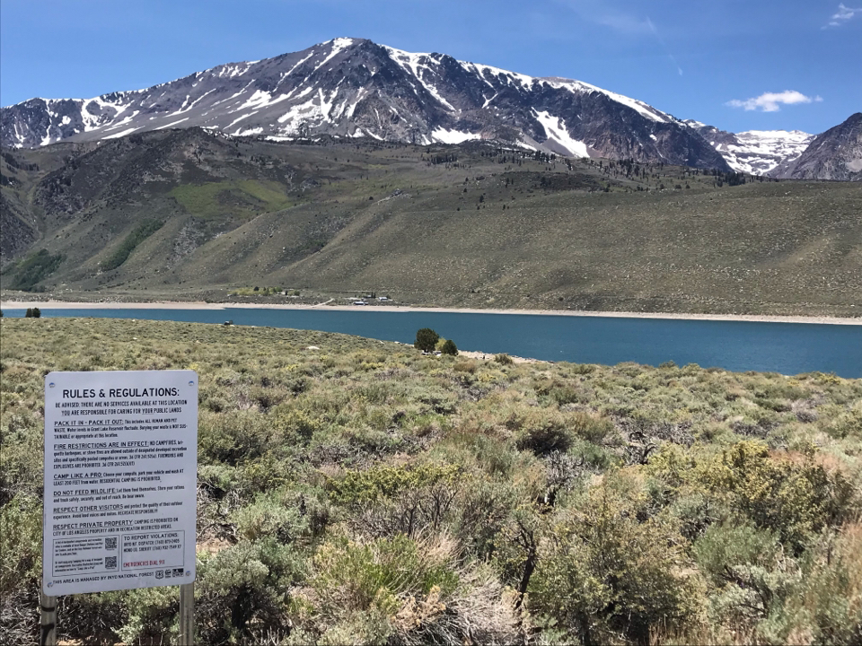 Image of a lake snowcapped mountains and a sign that reads rules and regulations