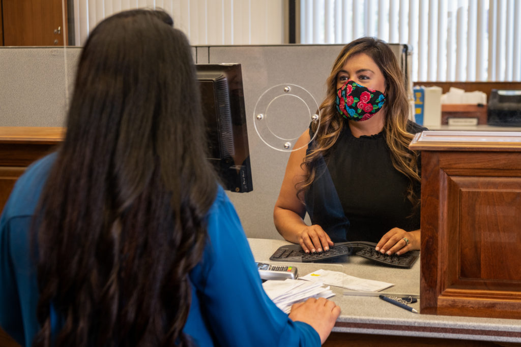 Image of a female customer service rep wearing a floral mask behind a plexiglass talking to a female customer with long dark hair.
