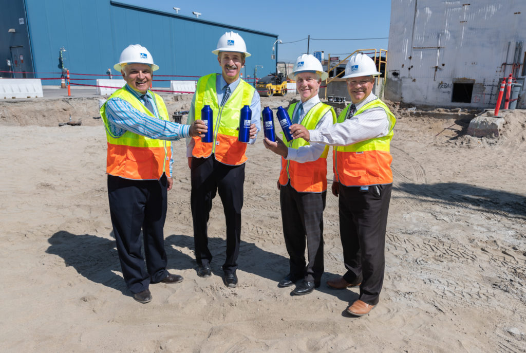 Image of four men in hard hats and construction vests holding blue water bottles