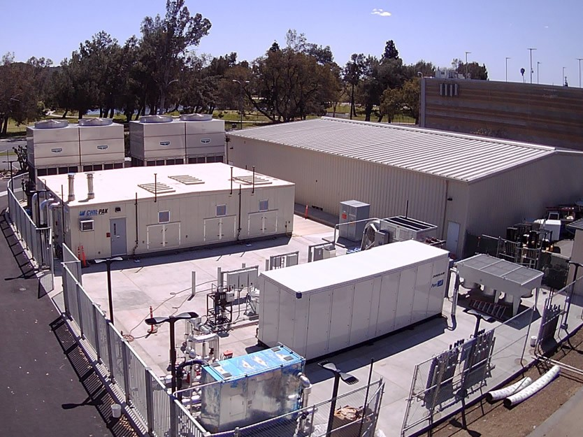 LA Mission College power plant showing various rectangular grey structures, pipes, ducts and cooling fans with a green tree laden landscape campus in the background