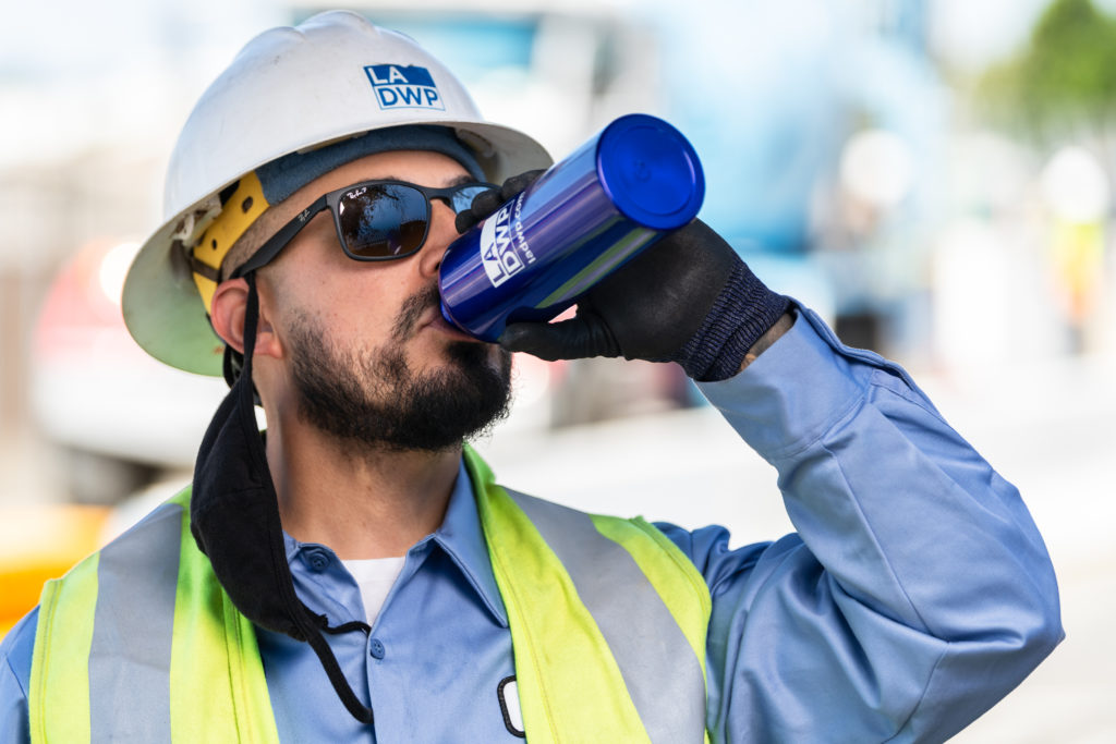 Male water utility worker with construction hardhat and yellow safety vest drinking water from reusable water bottle.