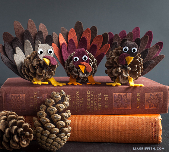 Felt and pine cone turkeys on books next to pine cones