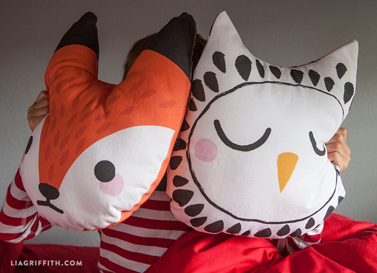 kid holding fox and owl DIY pillows