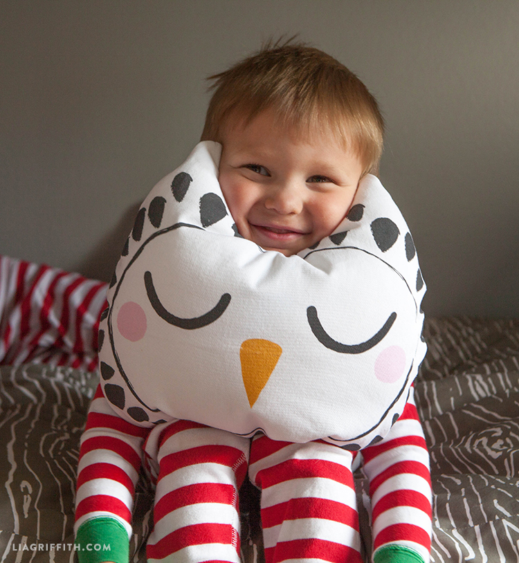 kid resting his face on owl pillow