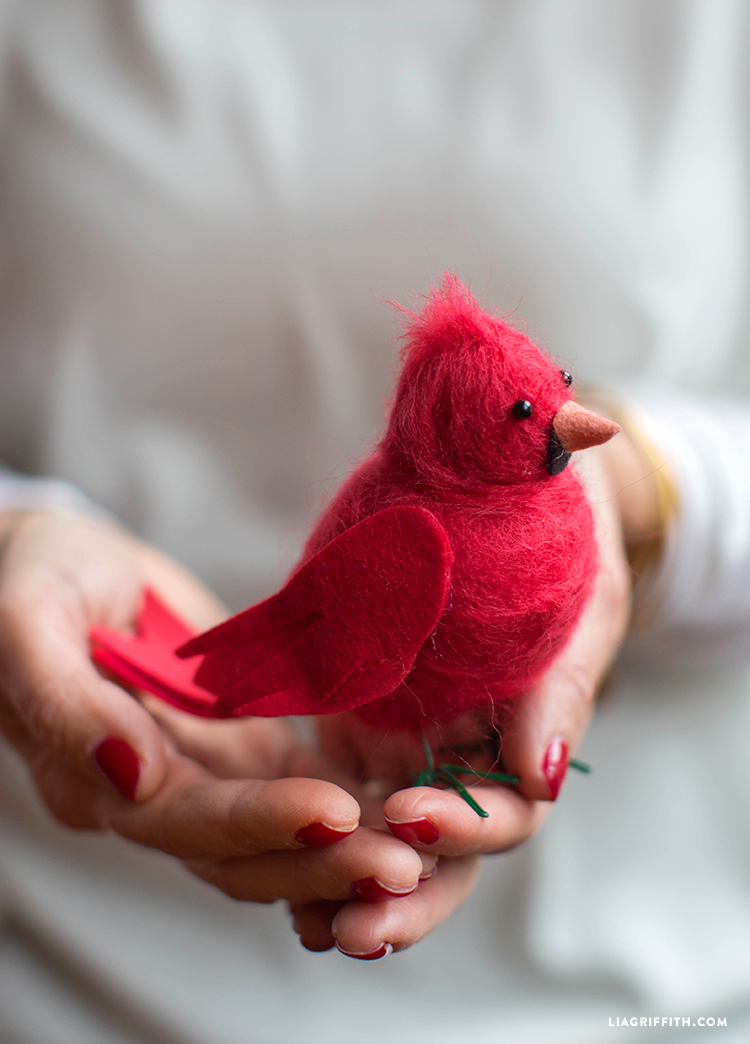 Woman holding felted cardinal bird in palm of hands