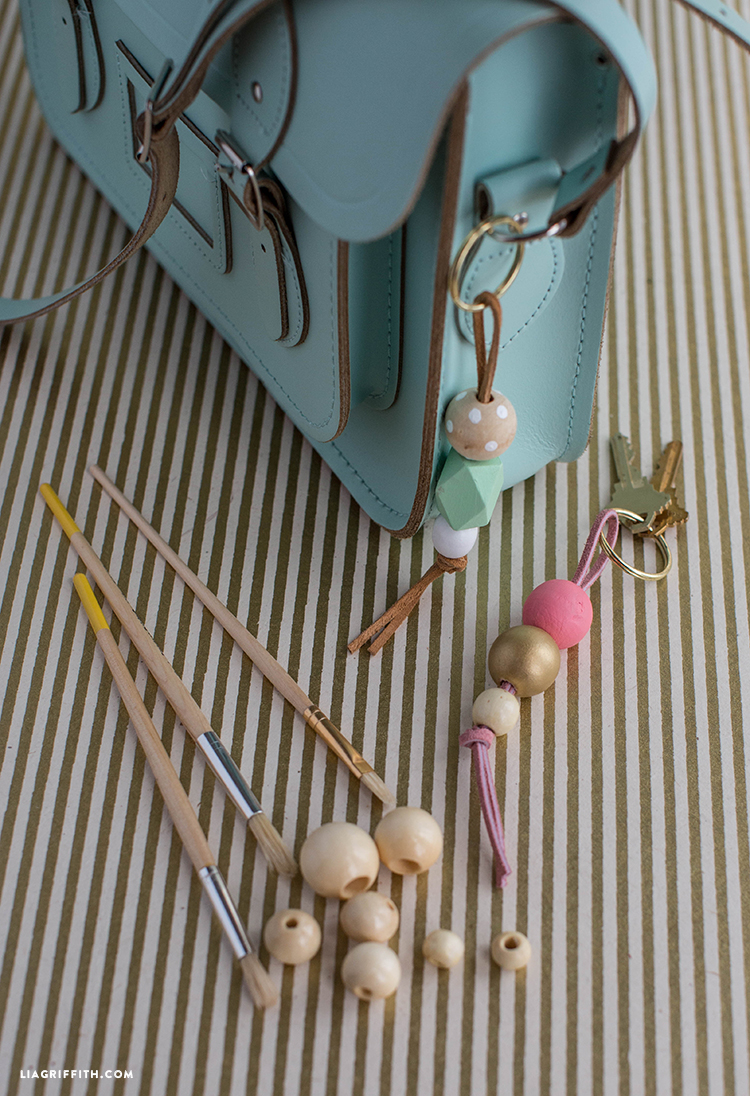 hand-painted keychain on purse next to wooden beads and paintbrushes