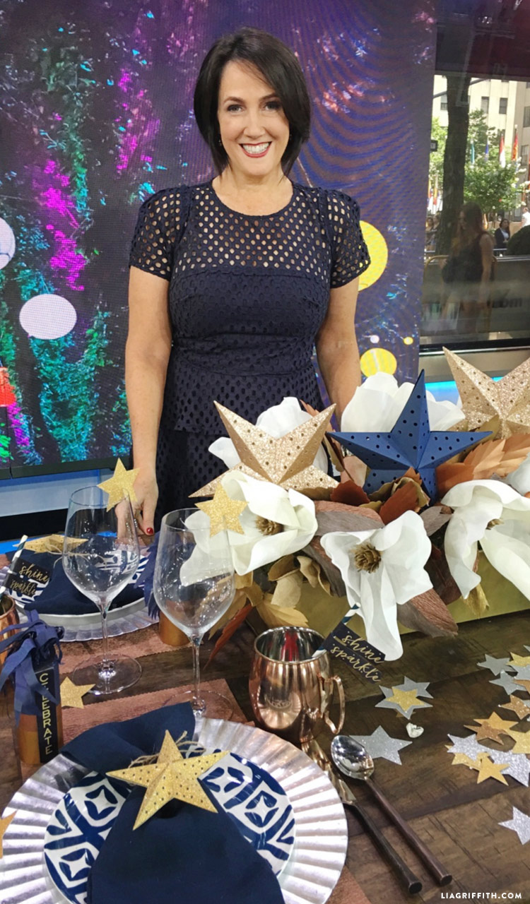 Lia Griffith standing in front of table with DIY 4th of July decorations, paper magnolia arrangement, and table settings