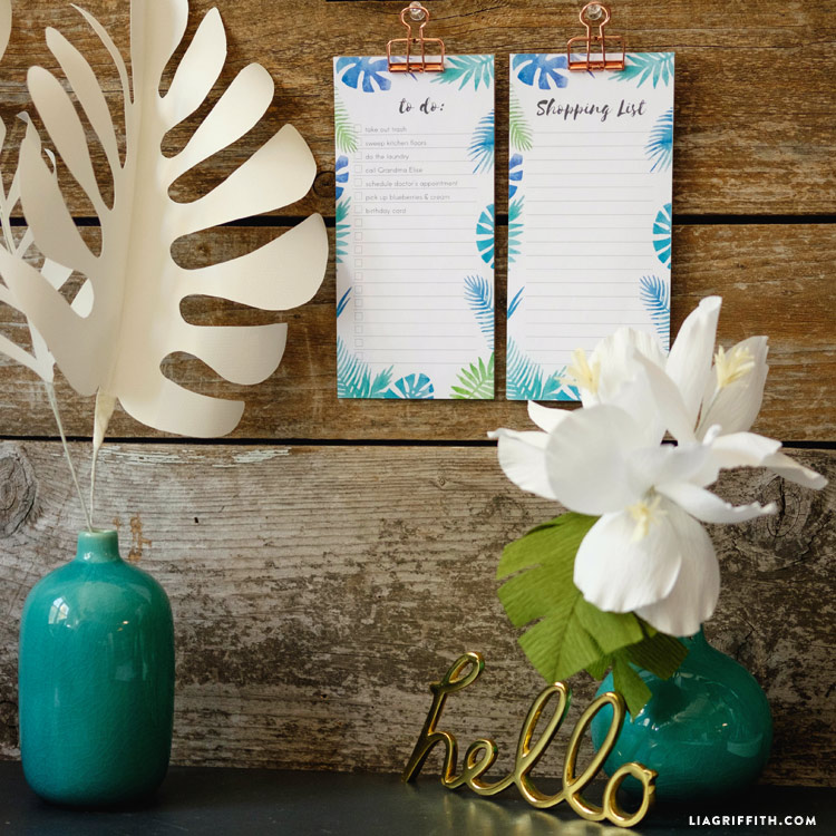 Tropical notepads on wall next to paper flower in vase and paper leaf in vase