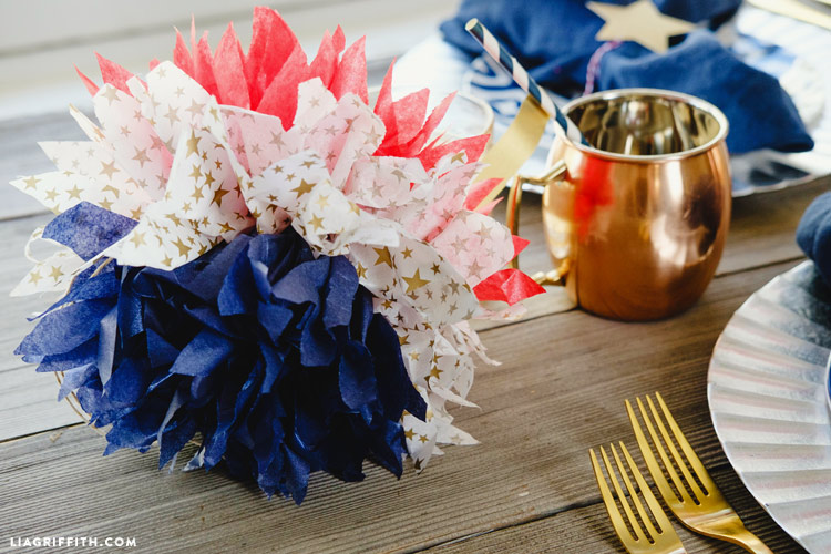 4th of July tissue pom poms on table with cup, forks, and plates on table