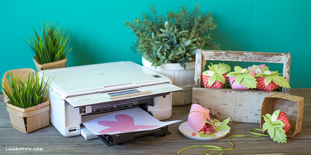Canon printer with strawberry treat box template next to plants and strawberry treat boxes