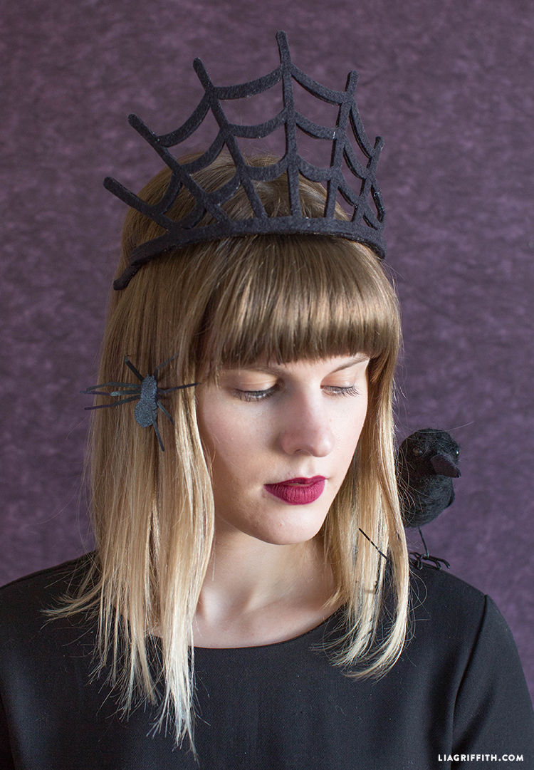 Woman wearing spiderweb crown with spiders in her hair and raven on shoulder