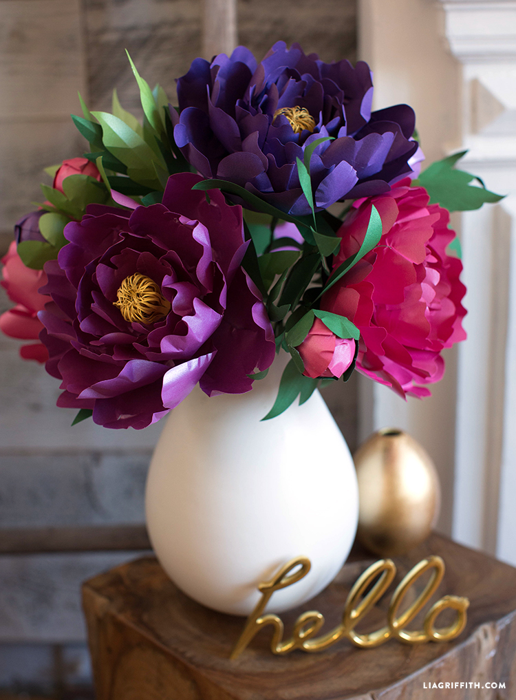 "Frosted paper peonies in white vase next to gold ""hello"" on side table"