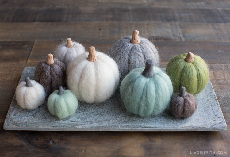 needle felted mini pumpkins in green, gray, mint, and white on tray