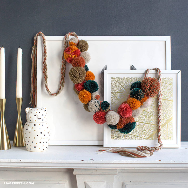 fall pom-pom garland hanging on art on mantel