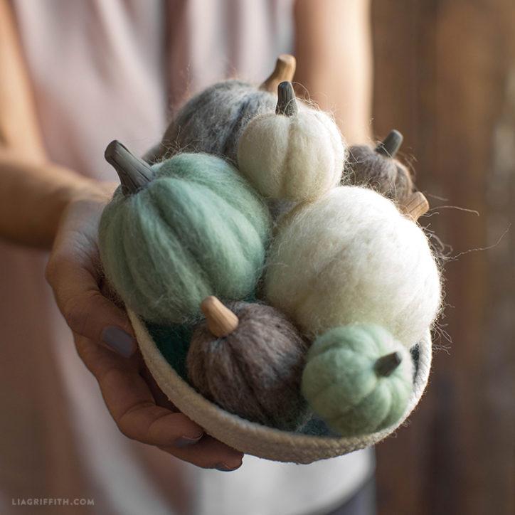 Woman holding basket of needle felted mini pumpkins