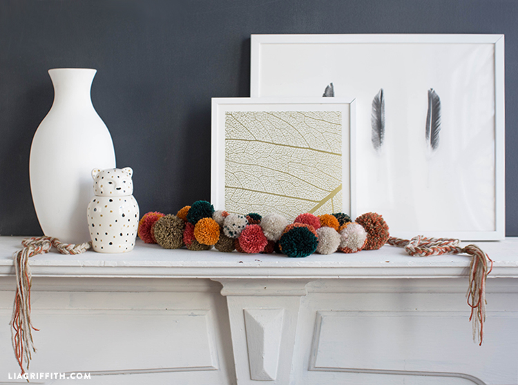 Fall pom-pom garland on mantel with vase and framed art