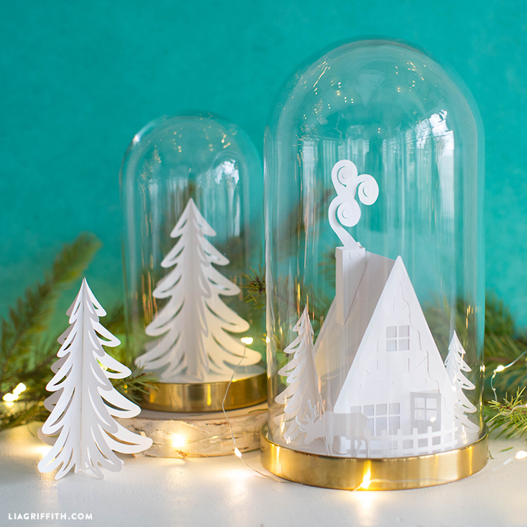 3D paper cabin in glass dome and paper tree in glass dome on mantel with tea lights