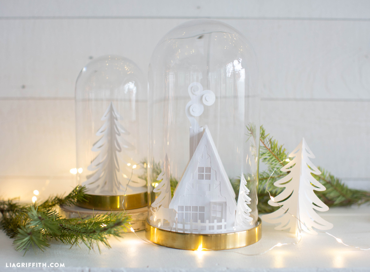 3D paper cabin in glass dome and paper tree in glass dome on mantel